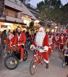 Nella foto di Foto KINO: Viale Ceccarini invaso dalla carica dei Babbo Natale, alla guida Babbo Natale in sella alla bicicletta ecologica Marcar & Bike